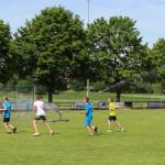 Leichtathleten laufen unter dem Rasensprenger und kühlen sich ab bei hochsommerlichen Temperaturen